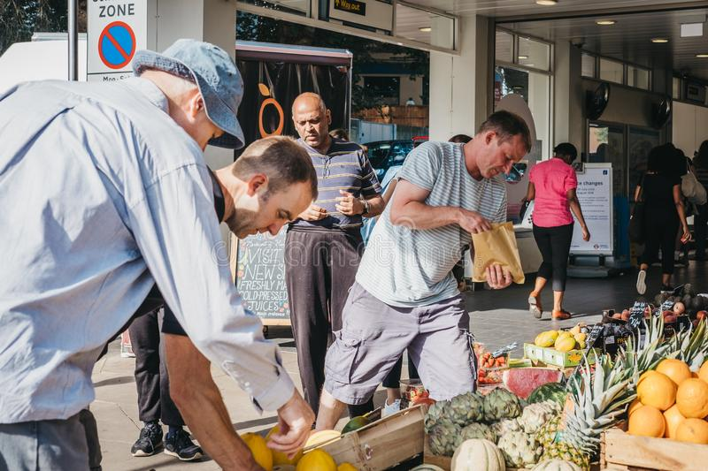 People buying fresh fruit at a stall outside Hampstead Heath Rail Station, London, UK. royalty free stock image