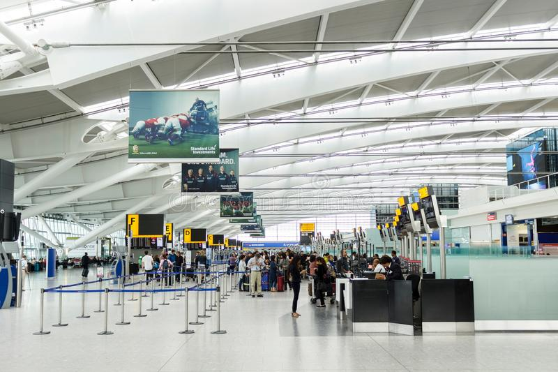 Heathrow Airport check in desks. LONDON, UK - CIRCA 2017: Passengers queue for check in at the departure hall in Terminal 5, Heathrow Airport stock image