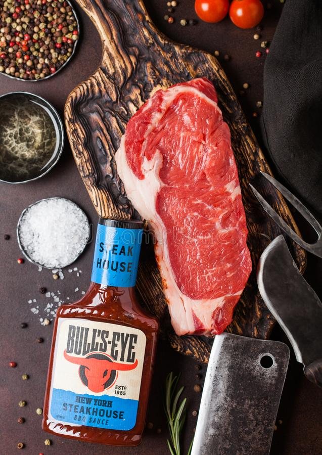 LONDON, UK - DECEMBER 13, 2018: Bottle of Bull`s Eye New York Stakehouse Barbeque sauce with raw sirloin beef steak on vintage. Chopping board with knife and royalty free stock photography