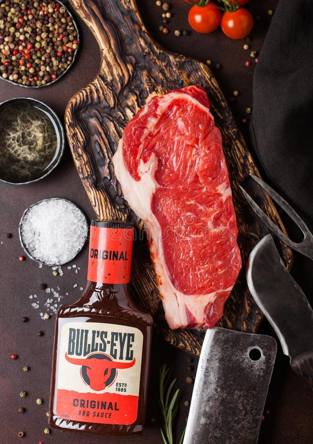 LONDON, UK - DECEMBER 13, 2018: Bottle of Bull`s Eye Original Barbeque sauce with raw sirloin beef steak on vintage chopping boar. D with knife and fork on rusty royalty free stock photos