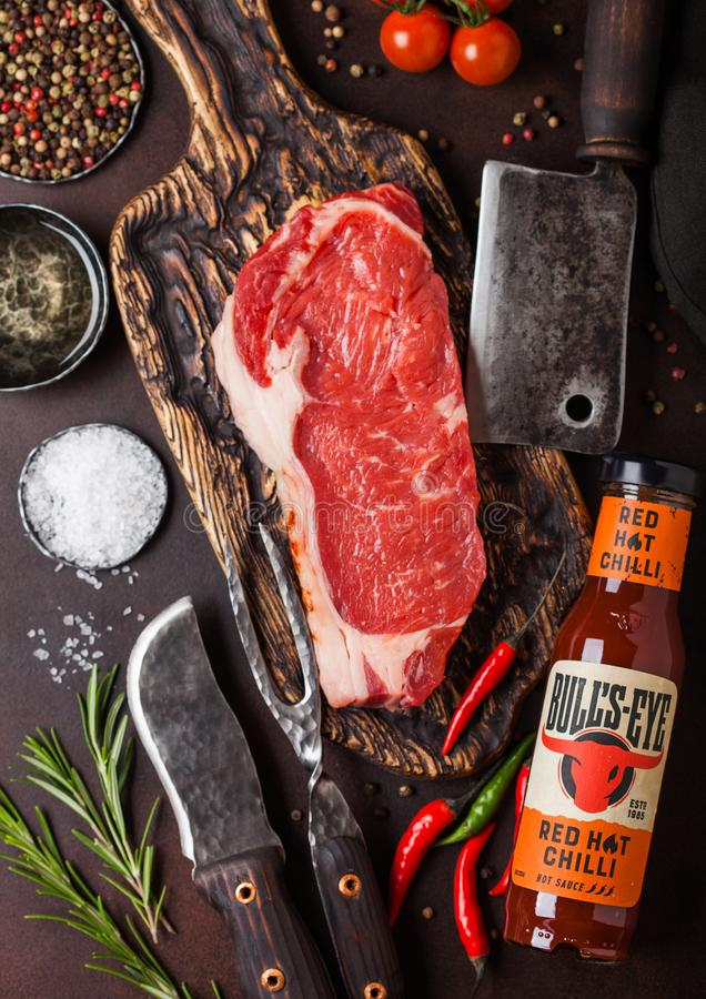 LONDON, UK - DECEMBER 13, 2018: Bottle of Bull`s Eye red hot chilli sauce with raw sirloin beef steak on vintage chopping board. With knife and fork on rusty stock image