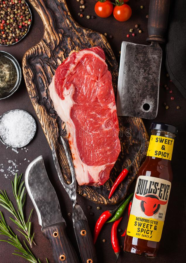 LONDON, UK - DECEMBER 13, 2018: Bottle of Bull`s Eye Sweet and Spicy sauce with raw sirloin beef steak on vintage chopping board. With knife and fork on rusty royalty free stock photo