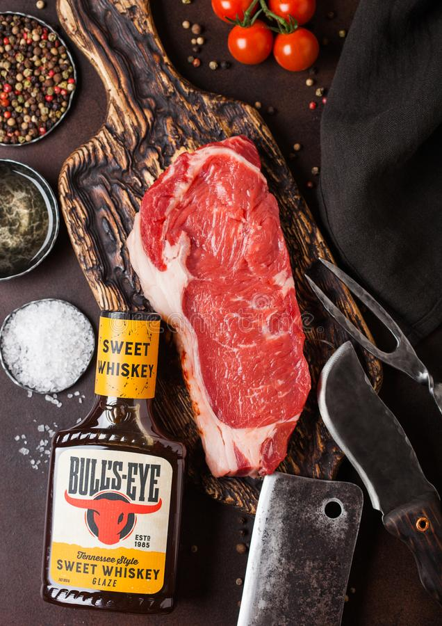 LONDON, UK - DECEMBER 13, 2018: Bottle of Bull`s Eye Tennessee style sweet whiskey sauce with raw sirloin beef steak on vintage. Chopping board with knife and stock image