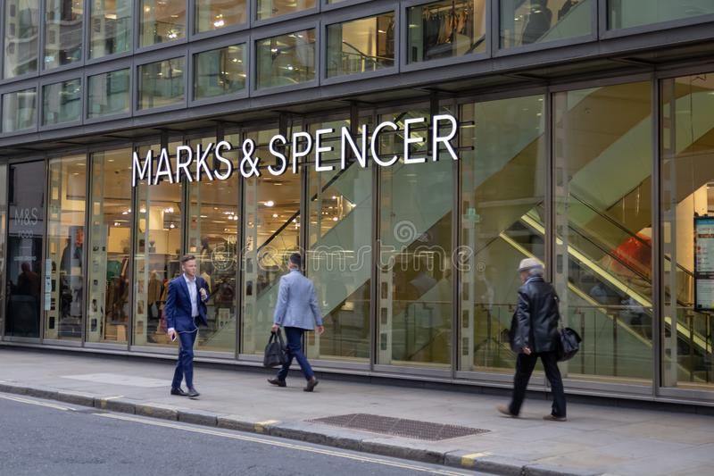 London, UK - 17, December 2018: Shoppers walking past the shop front to the Marks and Spencer department store in London royalty free stock photography