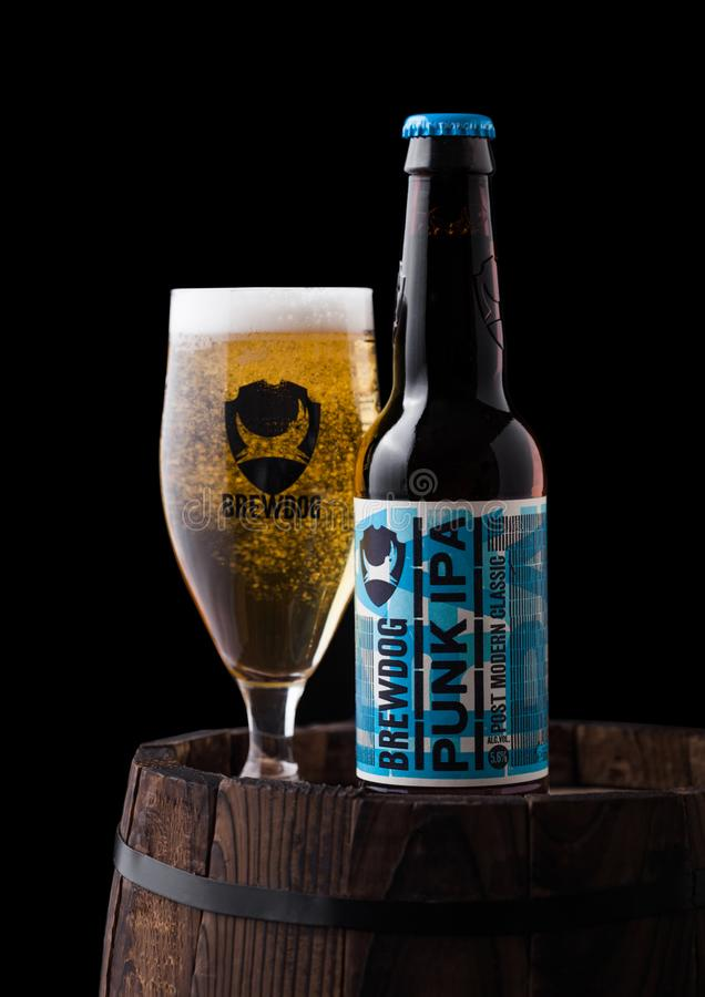 LONDON, UK - FEBRUARY 06, 2019: Bottle and glass of Punk IPA beer, from the Brewdog brewery on old wooden barrel on black. Background royalty free stock photos