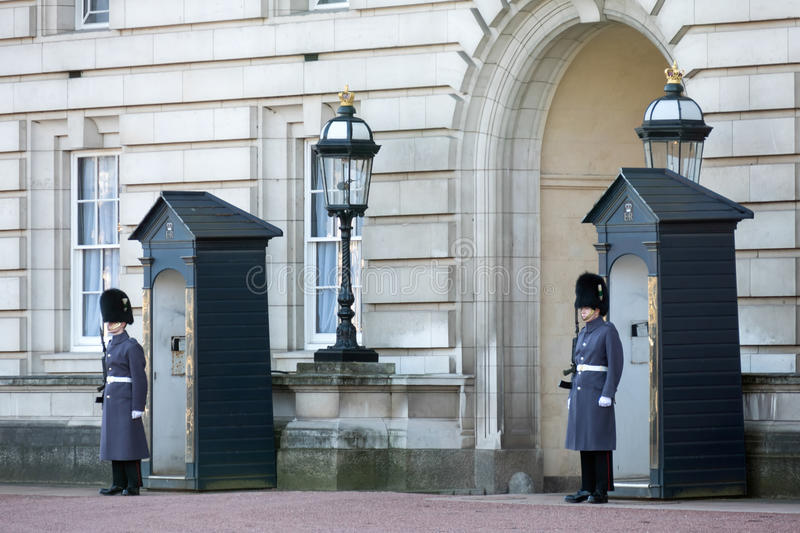LONDON/UK - FEBRUARY 18 : Guards in greatcoats on sentry duty at. Buckingham Palace in London on February 18, 2015. Unidentified people royalty free stock photo