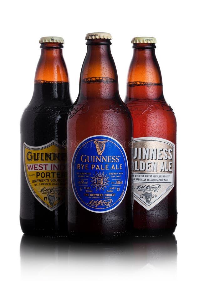 LONDON UK - JANUARI 02, 2018: Flaskor av Guinness rågljust öl, västra indiesportvakt och guld- ölöl på vit Guinness ölH arkivbilder