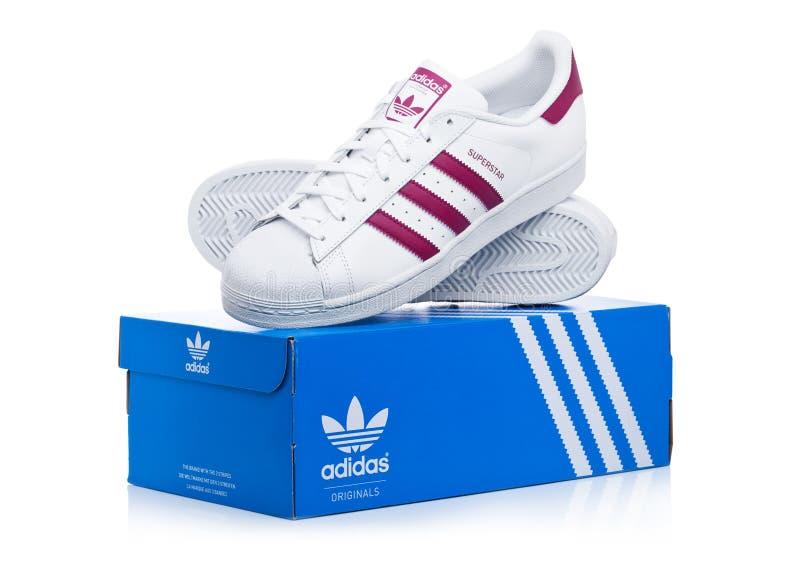 LONDON UK - JANUARI 12, 2018: Röda skor för Adidas originalvärldsstjärna med asken på vit Tysk multinationell korporation som pla royaltyfria bilder