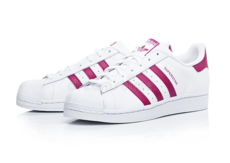 LONDON, UK - JANUARY 12, 2018: Adidas Originals Superstar red shoes on white.German multinational corporation that designs and man royalty free stock images