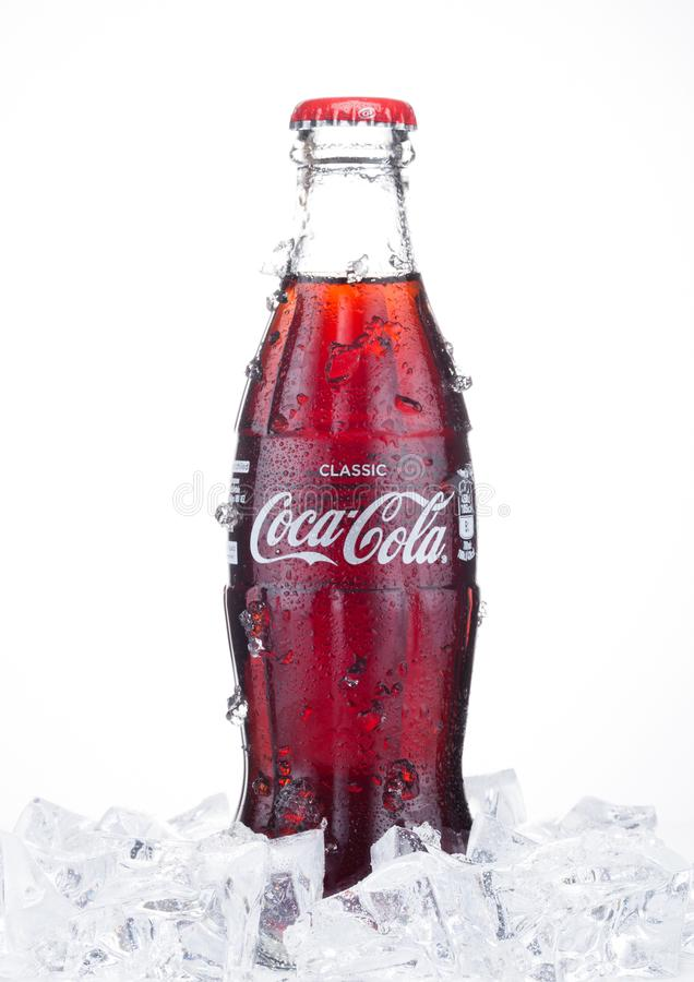 LONDON, UK - JANUARY 20, 2018: Cold glass bottle of Coca Cola drink with ice and dew on white. The drink is produced and manufact royalty free stock photography