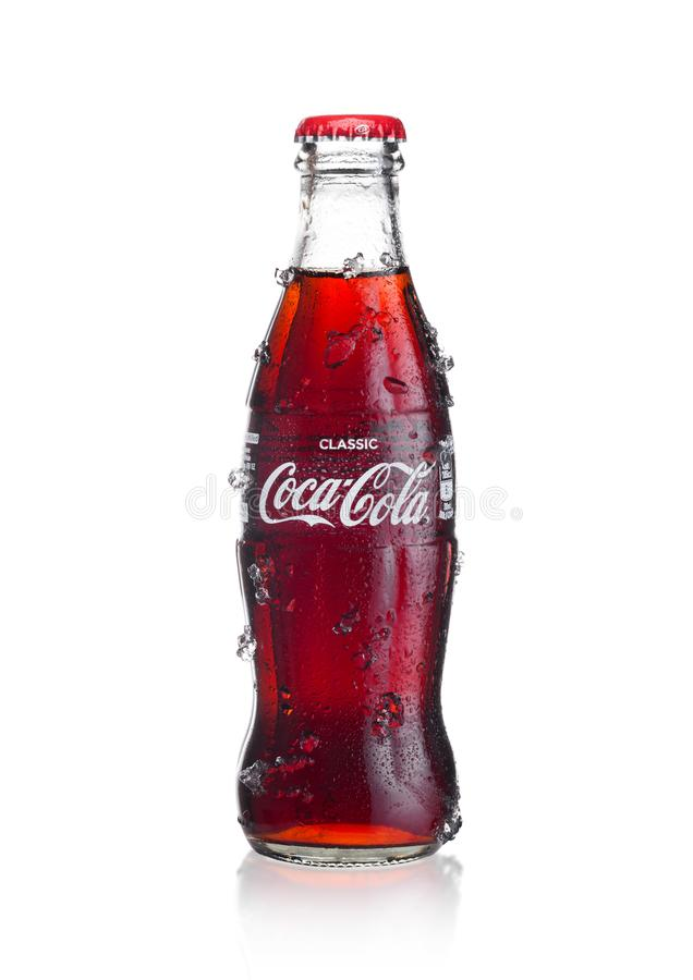 LONDON, UK - JANUARY 02, 2018: Cold glass bottle of Coca Cola drink with ice and dew on white. The drink is produced and manufact royalty free stock photography