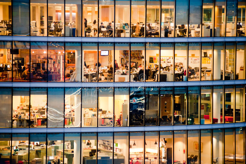 People working in an office building at night. Interior from the window stock photos