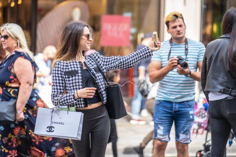 London UK, Juli 14, 2019 En flicka i London tar en selfie Utvalt fokusera royaltyfria foton