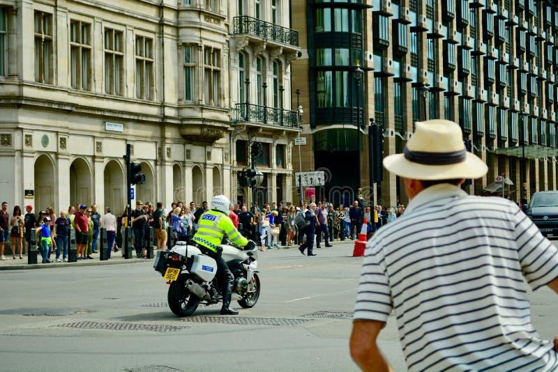 London UK, 21 Juli 2019 En polis på en reglerande trafik för polismotorcykel manuellt i stadsmitten Folkmassor av turisten royaltyfri bild