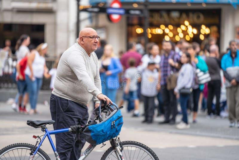 London UK, Juli 28, 2019 Manligt cyklistanseende med hans cykel på Piccadilly Circus royaltyfria foton