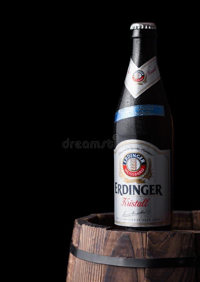 LONDON, UK - JULY 28, 2018: Bottle of Erdinger Kristall beer on top of wooden barrel on black. stock photography