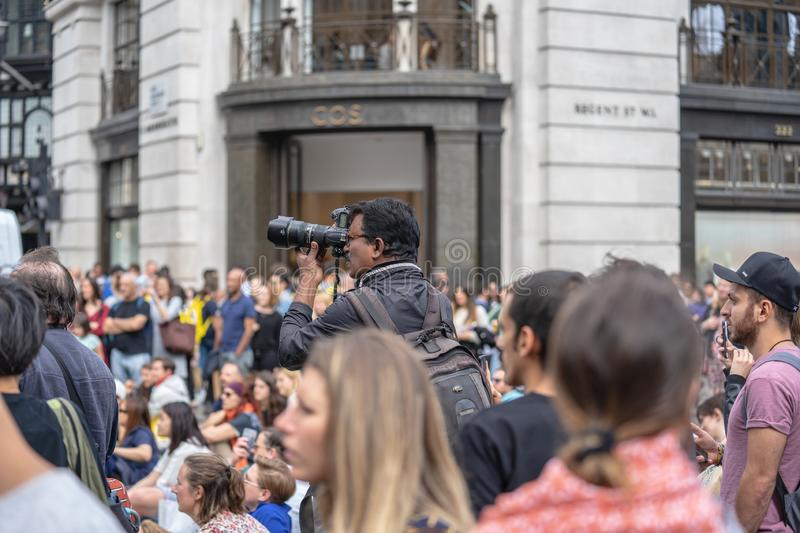 London, UK, July 14, 2019. Landscape and cityscape photographer taking pictures of free public event.  stock image