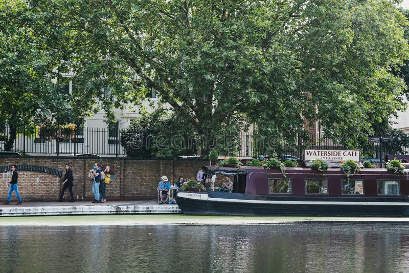 People walking past Waterside boat cafe moored on Regents Canal in Little Venice, London, UK. London, UK - July 18, 2019: People walking past Waterside boat cafe stock photo