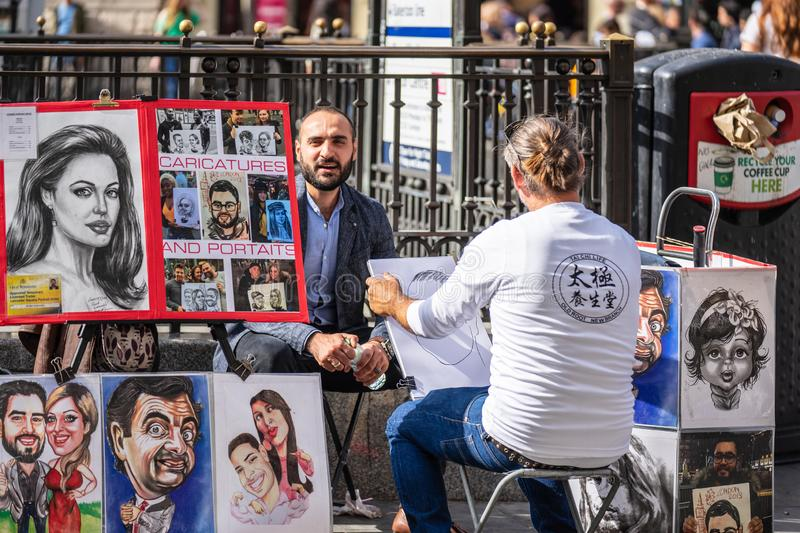 London, UK, July 14, 2019. The street artist is sketching models portrait. Caricaturist drawing people with different styles stock image
