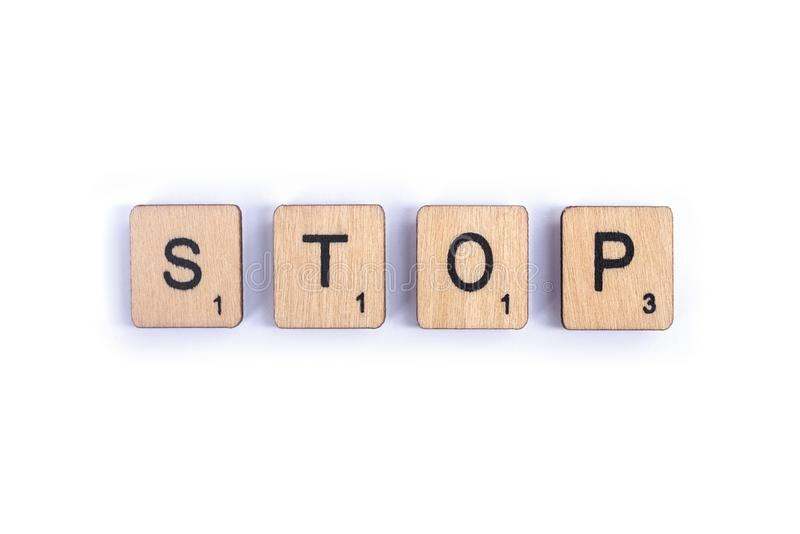 The word STOP. LONDON, UK - JULY 7TH 2018: The word STOP, spelt with wooden letter Scrabble tiles, on 7th July 2018 royalty free stock image
