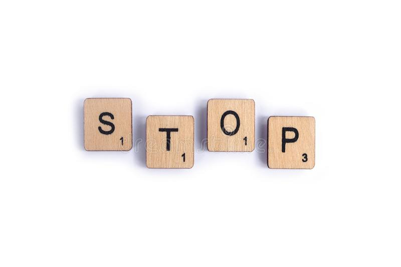 The word STOP. LONDON, UK - JULY 7TH 2018: The word STOP, spelt with wooden letter Scrabble tiles, on 7th July 2018 royalty free stock photography