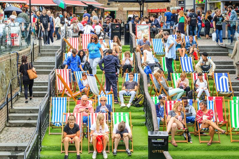 Tourist relaxing on deckchairs at crowded Camden Market in London royalty free stock photos