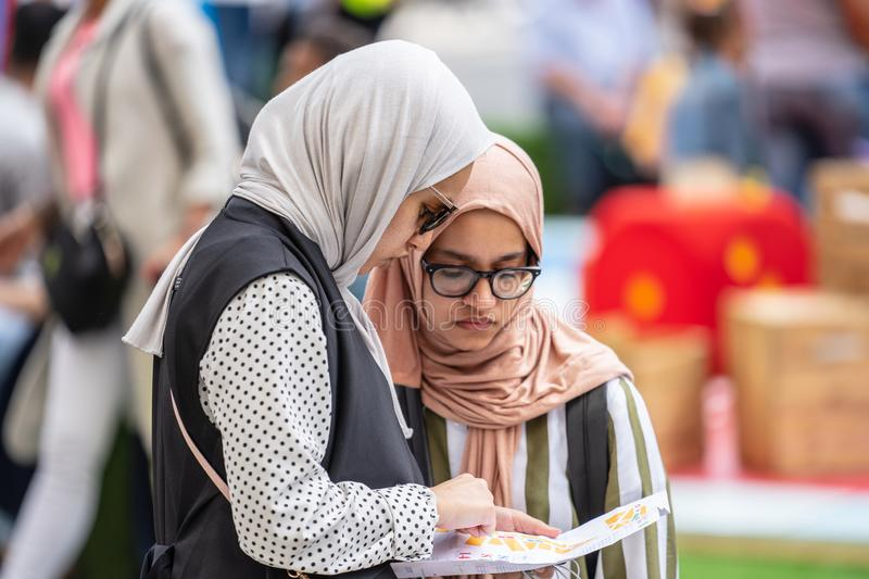 London, UK, July 14, 2019. Two female muslim tourists looking at the map. Regent Street royalty free stock images