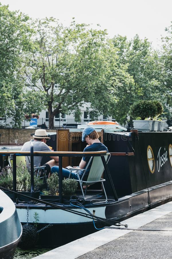 People relaxing and reading on a boat on Regents Canal in Little Venice, London, UK stock photography
