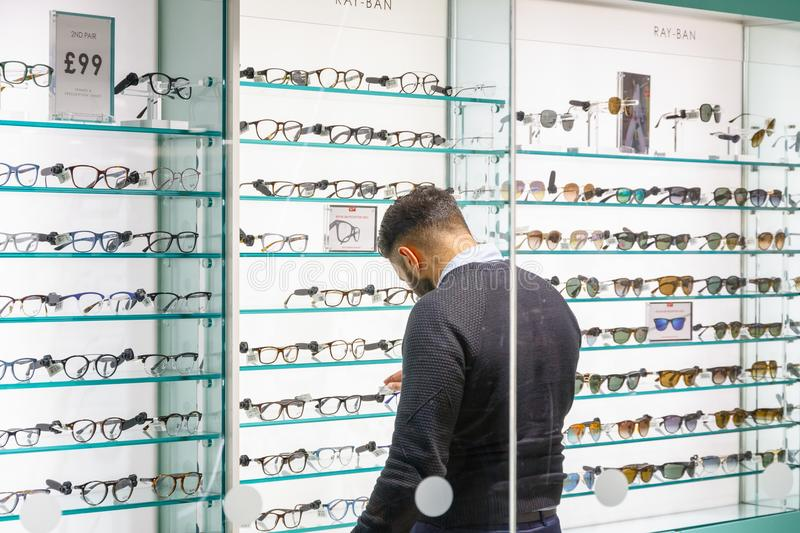 A man browsing glasses at an opticians in Canary Wharf royalty free stock image