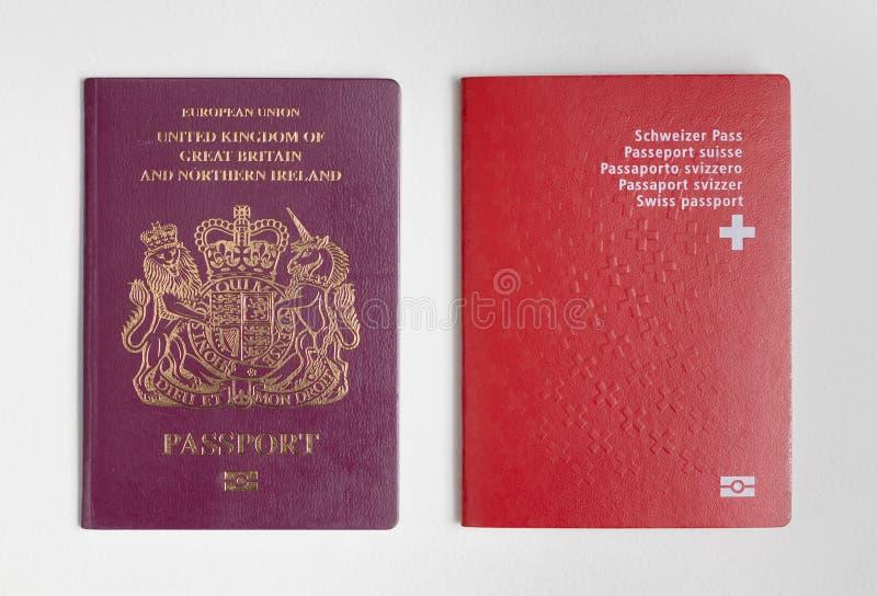 London / UK - June 21st 2019 - Swiss and UK passports, isolated on a white background.  royalty free stock image
