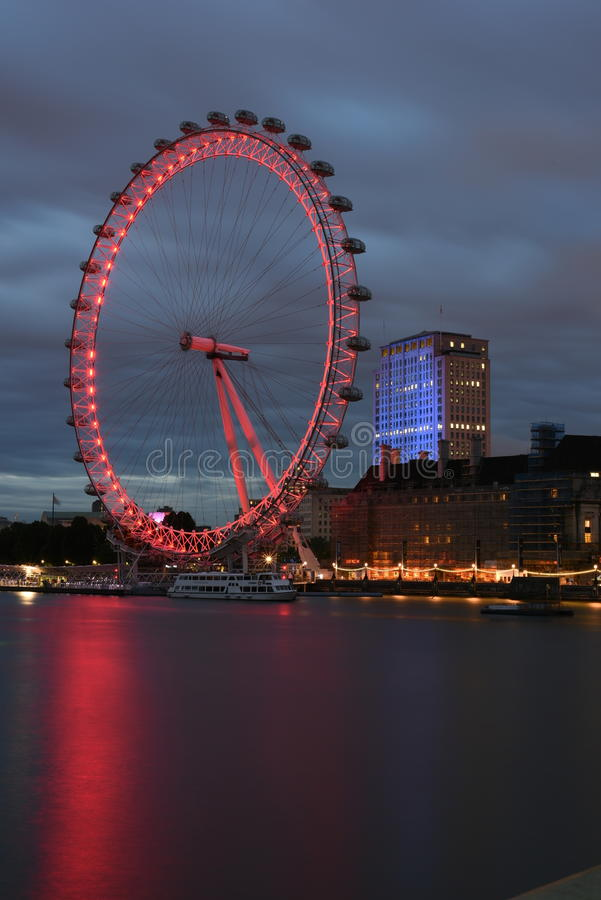 London UK:JUNE 26th 2015,Majestic London Eye and iconic buildings of London at night on the bank of River Thames royalty free stock photos