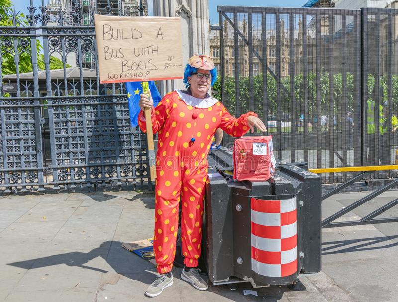 London / UK - June 26th 2019 - Pro-EU anti-Brexit protester dressed as a clown and holding `Build a bus with Boris` sign royalty free stock photos