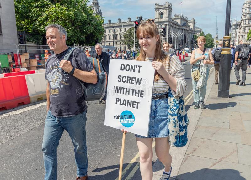 London/UK - Juni 26th 2019 - barnkvinnan bär ett klimatförändringtecken utanför parlamentet royaltyfri fotografi