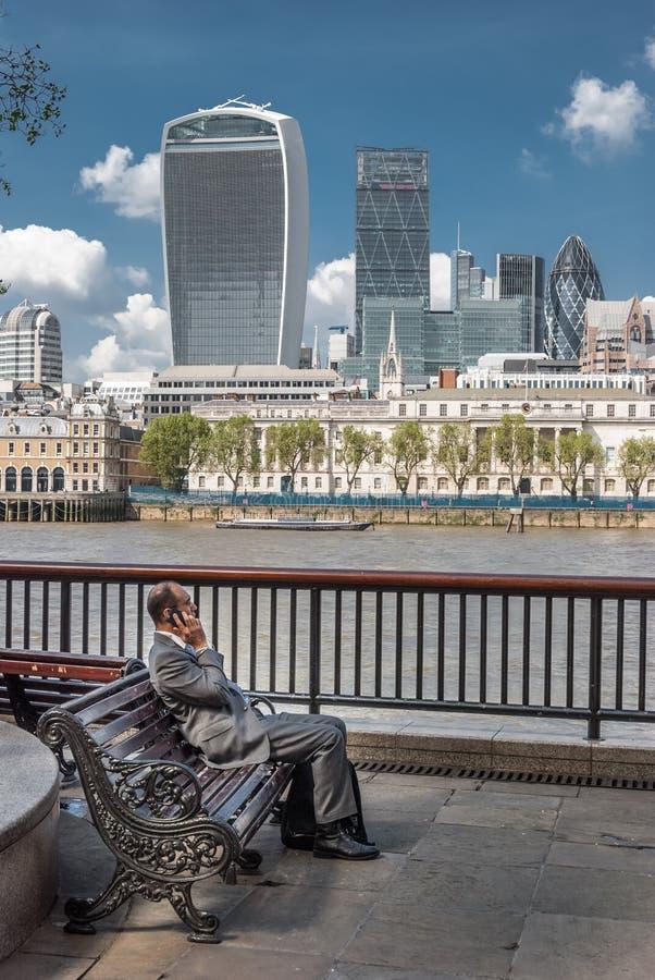 LONDON UK - MAJ 12, 2016: Den anpassade affärsmannen sitter på en bänk royaltyfria foton