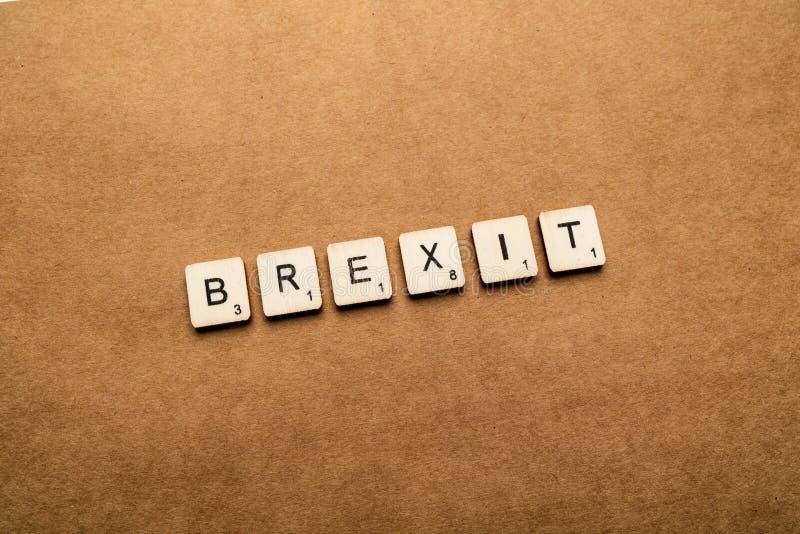 LONDON UK - Maj 24 2019: Ordet BREXIT som stavas med träbokstavstegelplattor över en brun texturerad bakgrund royaltyfri fotografi