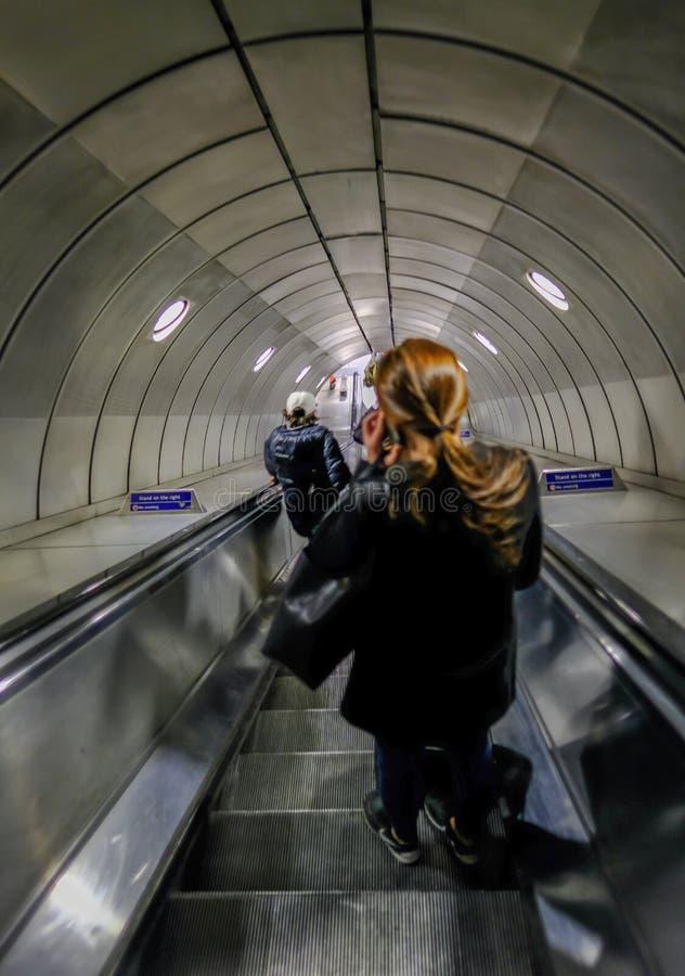 London UK - Maj 5, 2017: Passagerare som går ner rulltrappan fotografering för bildbyråer