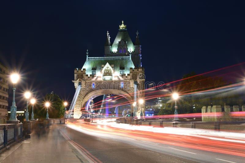 London UK, majestätisk tornbro på natten med ljusa slingor av bussen och bilar, konstnärligt långt exponeringsnattskott arkivfoton
