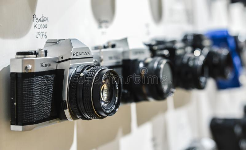 Close up of vintage film camera Pentax K1000 from 1976 with blurred background of other vintage cameras from the period. London, UK - Mar 6, 2018: Close up of royalty free stock photo