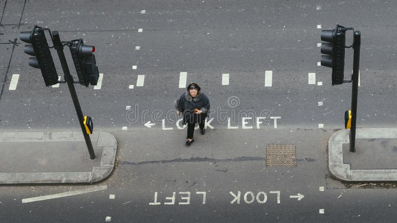 High perspective view of single woman in the City of London crossing the street. Iconic look left and look right signs. London, UK- Mar 13, 2018: High royalty free stock image