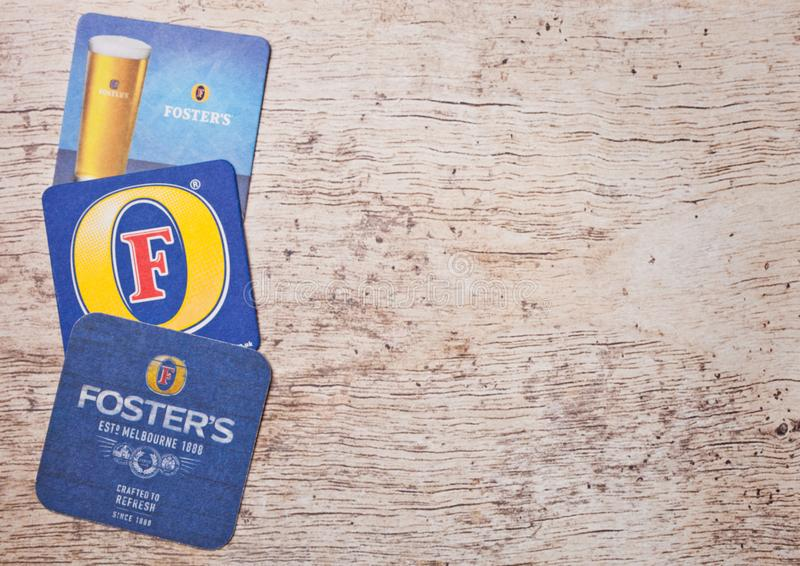 LONDON, UK - MARCH 22, 2018: Foster`s crafted beer original beermat coaster on wood. stock photo
