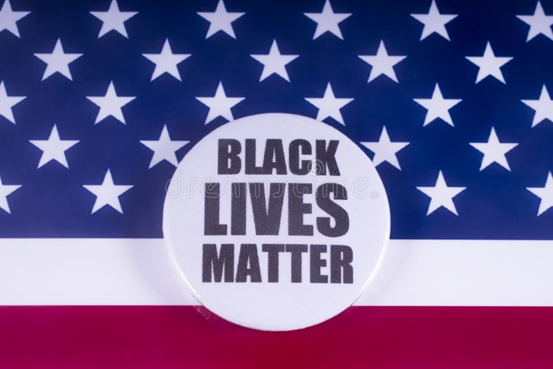 Black Lives Matter Badge over the USA Flag. LONDON, UK - MARCH 18TH 2018: A Black Lives Matter badge over a US flag background, on 18th March 2018. BLM is an stock image