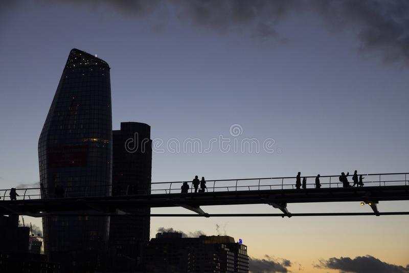 London cityscape across the River Thames with a view of people crossing the Millennium Bridge, London,. LONDON, UK - MAY 20, 2017. London cityscape across the royalty free stock photos