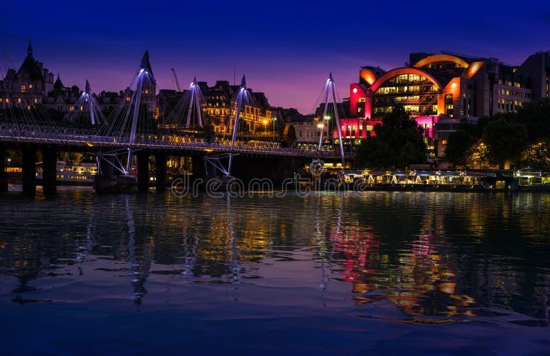 london uk 22nd Maj 2017 Spången för för den Charing korsstationen och femtioårsjubileet reflekterar i flodThemsen på natten arkivbild