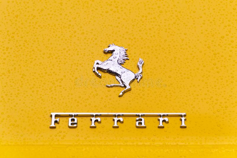 London, UK - November 2019: A close-up of the Ferrari logo on a yellow car with drops of water royalty free stock images
