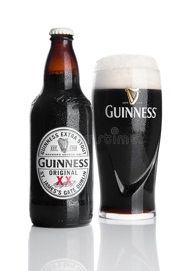 LONDON, UK - NOVEMBER 29, 2016: Guinness extra stout beer bottle and glass on white background. Guinness beer has been produced s royalty free stock photos