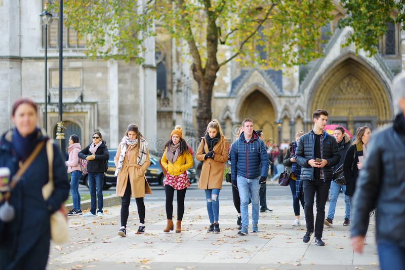 LONDON, UK - NOVEMBER 19, 2017: Lots of tourists and Londoners walking down the streets and crossing the junctions. royalty free stock image