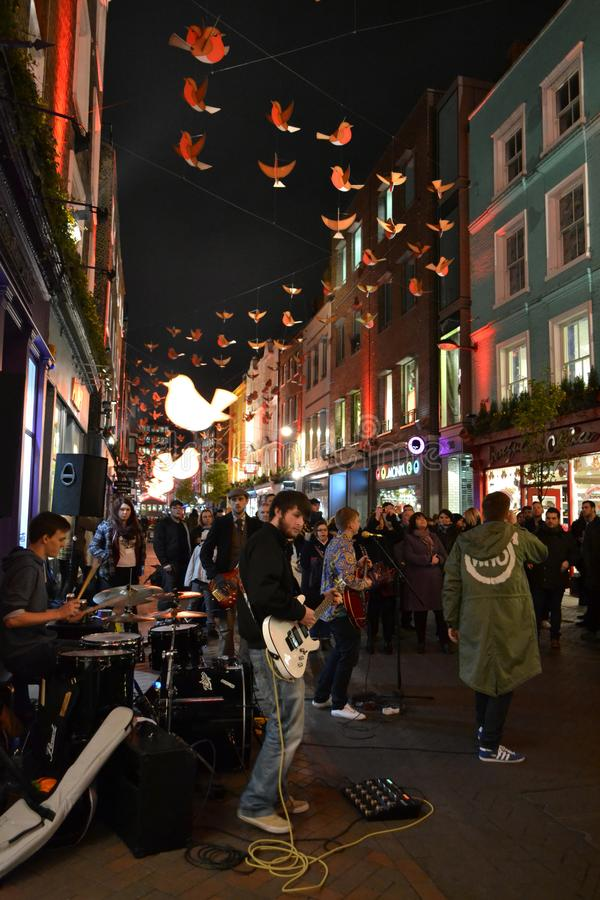 Music band is playing in the London Carnaby street decorated for Christmas holidays and brightly illuminated by night. royalty free stock images