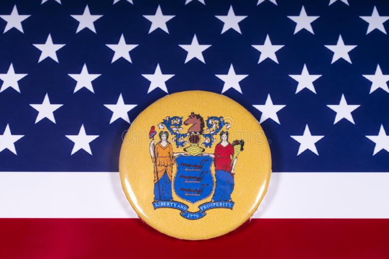 The State of New Jersey in the USA. London, UK - November 15th 2018: The coat of arms of the State of New Jersey, pictured over the flag of the United States of royalty free stock photos