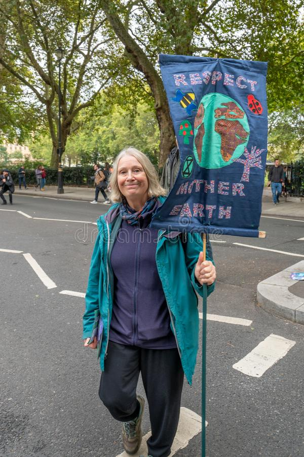 London, UK - October 7, 2019: Participants of the protest rally Extinction Rebellion - woman with a banner royalty free stock photography