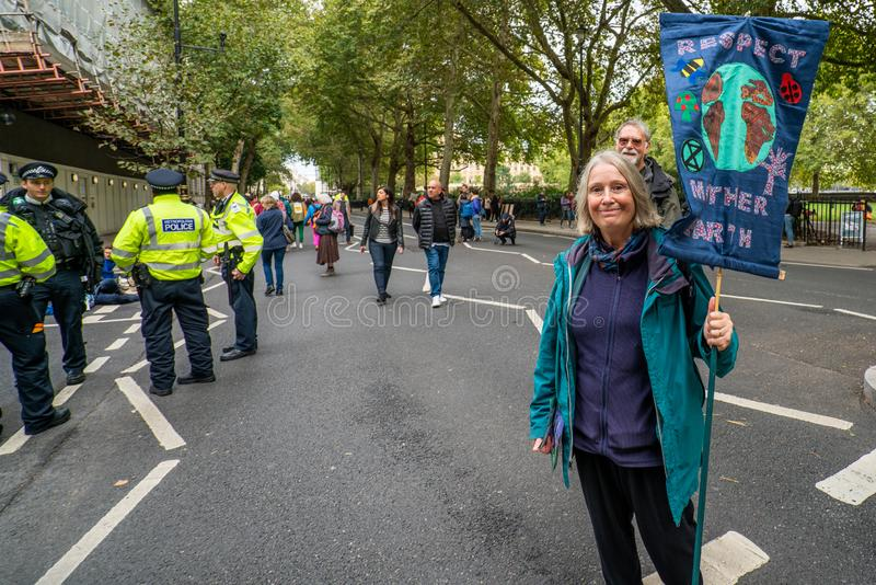 London, UK - October 7, 2019: Participants of the protest rally Extinction Rebellion - woman with a banner royalty free stock photos